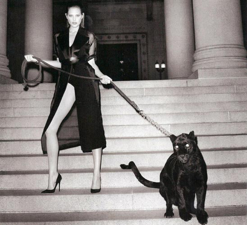 A chained black leopard posing with a model for a Harpers Bazaar photoshoot in 2013.